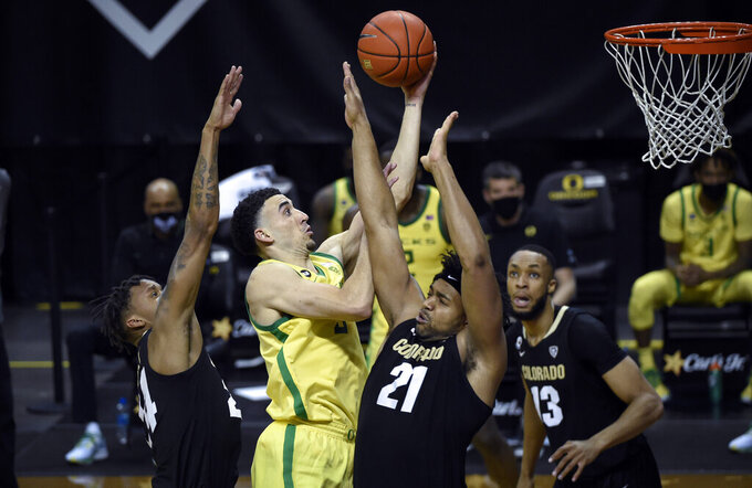 Oregon guard Chris Duarte (5) drives past Colorado guard Eli Parquet (24) and forward Evan Battey (21) as Colorado forward Dallas Walton (13) watches during the second half of an NCAA college basketball game Thursday, Feb. 18, 2021, in Eugene, Ore. (AP Photo/Andy Nelson)