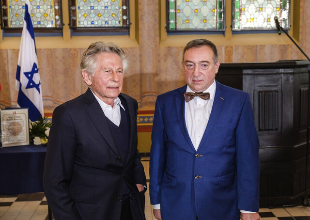 Oscar-winning filmmaker Roman Polanski, left, poses for the media with Stanislaw Buchala, right, who received the Israeli distinction of the Righteous Among the Nations on behalf of his late grandparents, Stefania and Jan Buchala, who saved Polanski, from the Holocaust in 1943-45, during the ceremony of bestowing the honor in Gliwice, Poland, on Thursday, Oct. 15, 2020.(AP Photo/Michal Buksa)