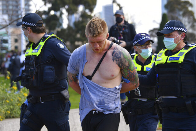 Police arrest a man as people gather at a so-called