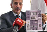 In this photo released by the Syrian official news agency SANA, Iyed Bilal, the director of the treasury department of the Syrian Central Bank, shows an information sheet about the new banknote of 5000 Syrian pounds during a press briefing, in Damascus, Syria, Sunday, Jan. 24, 2021. A new 5,000 Syrian Lira bank note goes into circulation Sunday, the largest denomination in the country reeling from 10 years of conflict and a crippling economic crisis. (SANA via AP)