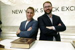 Slack Technolegies co-founders Stewart Butterfield, left, and Cal Henderson pose for photos on the New York Stock Exchange trading floor before their company's IPO, Thursday, June 20, 2019. (AP Photo/Richard Drew)