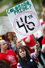 Karen Ann Green, a retired teacher, holds up a placed during a rally outside the State Capitol Monday, April 16, 2018, in Denver. Teachers from around the state were on hand to demand better salaries as lawmakers under the dome were set to debate a pension reform measure to cut retirement benefits as well as take-home pay. (AP Photo/David Zalubowski)