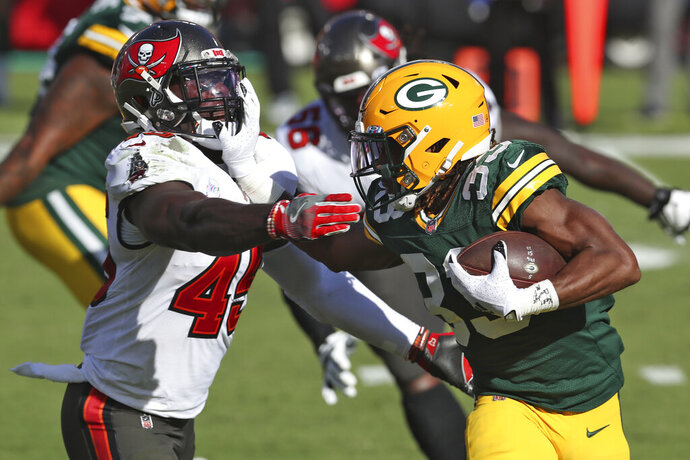 Green Bay Packers running back Aaron Jones (33) stiff arms Tampa Bay Buccaneers inside linebacker Devin White (45) during the first half of an NFL football game Sunday, Oct. 18, 2020, in Tampa, Fla. (AP Photo/Mark LoMoglio)