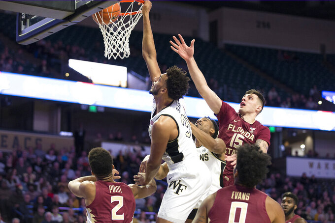 Wake Forest's Olivier Sarr (30) dunks over Florida State players in the first half of an NCAA college basketball game Wednesday, Jan. 8, 2020 in Winston-Salem, N.C. (AP Photo/Lynn Hey)