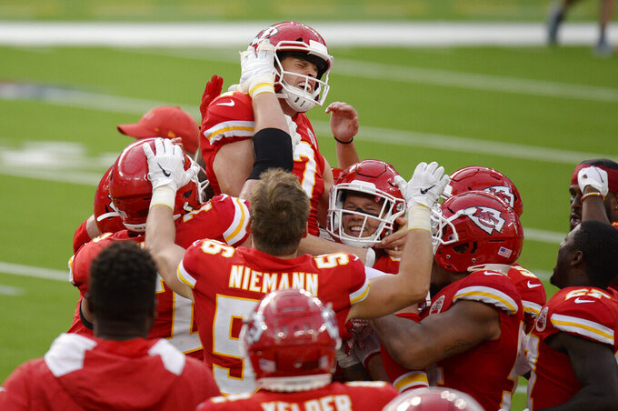 Kansas City Chiefs kicker Harrison Butker, top, is lifted by teammates after making the game-winning field goal during overtime of an NFL football game against the Los Angeles Chargers Sunday, Sept. 20, 2020, in Inglewood, Calif. Kansas City won 23-20. (AP Photo/Kyusung Gong)