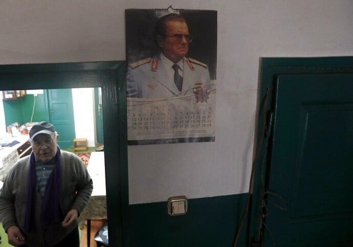 In this photo taken on Thursday, Jan. 23, 2020, Uros Trainovic walks inside his house decorated with picture of former Yugoslav communist president Josip Broz Tito, in the village of Blagojev Kamen, Serbia. Near-empty villages with abandoned, crumbling houses can be seen all over Serbia — a clear symptom of a shrinking population that is raising acute questions over the economic well-being of the country. The decline is happening so fast it's considered a national emergency and the United Nations has stepped in to help. (AP Photo/Darko Vojinovic)