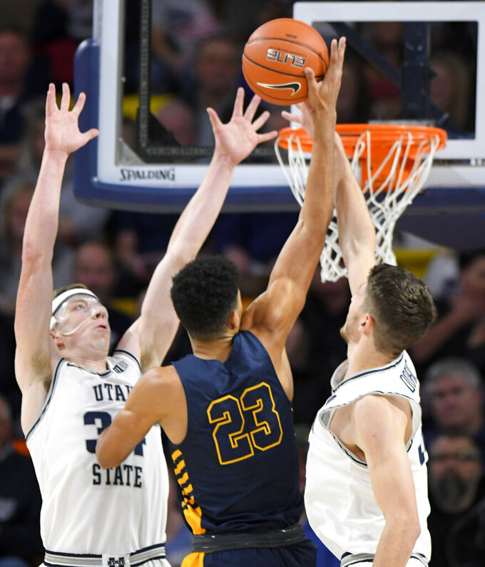 North Carolina A&T forward Devin Haygood (23) shoots as Utah State forward Justin Bean (34) and center Trevin Dorius defend during the first half of an NCAA college basketball game Friday, Nov. 15, 2019, in Logan, Utah. (AP Photo/Eli Lucero)