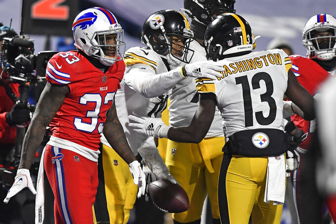 Pittsburgh Steelers wide receiver JuJu Smith-Schuster (19) celebrates with James Washington (13) after taking a 3-yard touchdown pass from quarterback Ben Roethlisberger as Buffalo Bills safety Siran Neal (33) heads back to the sideline during the second half of an NFL football game in Orchard Park, N.Y., Sunday, Dec. 13, 2020. (AP Photo/Adrian Kraus)