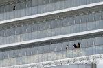 The passengers stand on the balcony of the quarantined Diamond Princess cruise ship docked at a port in Yokohama, near Tokyo, Wednesday, Feb. 19, 2020. The cruise ship begins letting passengers off the boat on Wednesday after it's been in quarantined for 14 days. (AP Photo/Eugene Hoshiko)