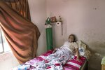 Clara Reina Villacorta, 74, who is infected with the COVID-19 virus, breathes in oxygen inside her home in the Villa El Salvador neighborhood of Lima, Peru, Tuesday, April 6, 2021, amid the new coronavirus pandemic. (AP Photo/Rodrigo Abd)