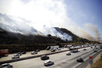 Smoke from a wildfire engulfs a hillside as traffic flows along I-5 Freeway Saturday, Oct. 12, 2019, in Newhall, Calif. The smoky scent spreading through much of Los Angeles was a reminder of the threat of a fire season just beginning. (AP Photo/Marcio Jose Sanchez)