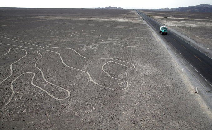 Driver Gerard De Rooy, of Netherlands, and co-drivers Darek Rodewald, of Poland, and Moises Torrallardona, of Spain, drive their Iveco truck along the Nazca Lines geoglyphs in Nazca, Peru, after finishing second in the second stage of the Dakar Rally between Pisco and San Juan de Marcona, Tuesday, Jan. 8, 2019. (AP Photo/Ricardo Mazalan)