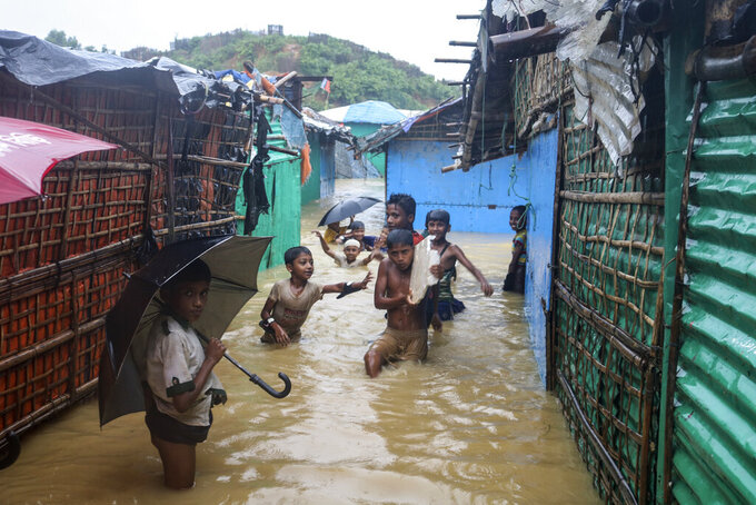 Rohingya refugee children play in flood waters at the Rohingya refugee camp in Kutupalong, Bangladesh, Wednesday, July 28, 2021. Days of heavy rains have brought thousands of shelters in various Rohingya refugee camps in Southern Bangladesh under water, rendering thousands of refugees homeless. (AP Photo/ Shafiqur Rahman)
