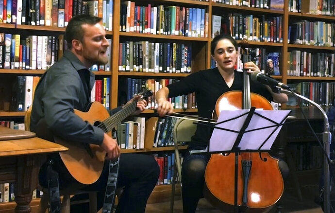 In this Oct. 10, 2018 still image from video provided by Gregory Tatro, Republican Zac Mayo, left, plays the guitar and Democrat Lucy Rogers, right, plays the cello as they perform a duet at the end of a forum at the Varnum Memorial Library in Jeffersonville, Vt. The duo are running against each other in the November general election, seeking to represent rural Lamoille County in the Vermont House. Rogers came up with the idea after learning during the primary election that Mayo also was a musician. (Gregory Tatro via AP)