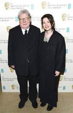 """FILE - Director Alan Parker and his wife, Lisa arrive for the BAFTA Film Awards in London on Feb. 10, 2013. Parker, whose movies included """"Bugsy Malone,"""" """"Midnight Express"""" and """"Evita,"""" has died at the age of 76. A statement from the director's family says Parker died Friday in London after a long illness. (Photo by Jon Furniss/Invision/AP, File)"""