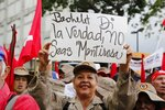 A member of the Bolivarian militia holds up a sign with a message that reads in Spanish: