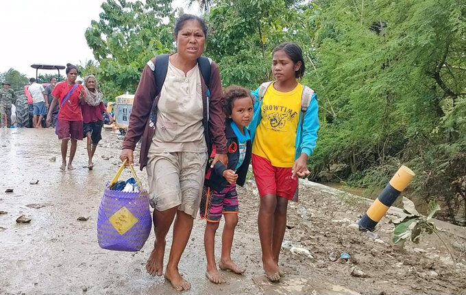 A woman with her children carries their belongings as they walk after crossing a flooded road in Malaka Tengah, East Nusa Tenggara province, Indonesia, Monday, April 5, 2021. Multiple disasters caused by torrential rains in eastern Indonesia have left dozens of people dead and missing and displaced thousands, the country's disaster relief agency said Monday. (AP Photo)