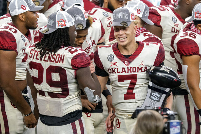 Oklahoma quarterback Spencer Rattler (7) is congratulated by running back Rhamondre Stevenson (29) as he holds the Most Outstanding Player trophy after their 27-21 win over Iowa State in the Big 12 Conference championship NCAA college football game, Saturday, Dec. 19, 2020, in Arlington, Texas. (AP Photo/Jeffrey McWhorter)