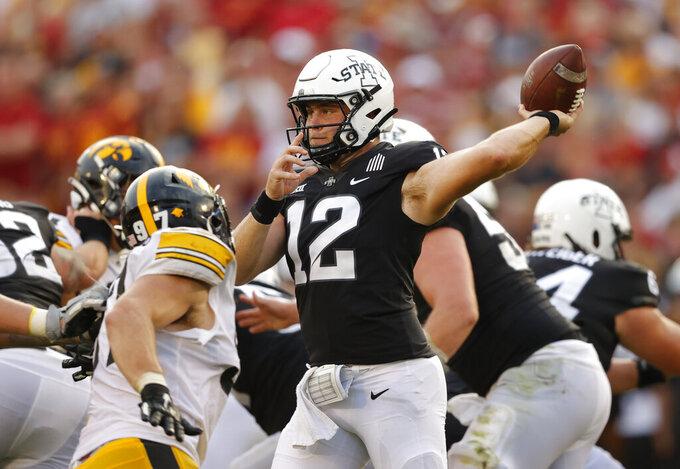 Iowa State quarterback Hunter Dekkers (12) sends a pass downfield as Iowa defensive lineman Zach VanValkenburg (97) pressures during the second half of an NCAA college football game, Saturday, Sept. 11, 2021, in Ames, Iowa. Iowa won 27-17. (AP Photo/Matthew Putney)