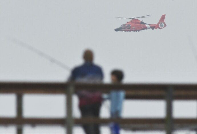 People fish on a pier as a U.S. Coast Guard helicopter searches the coastline for a small plane that may have crashed in Santa Barbara, Calif., Sunday, Sept. 27, 2020. Officials with Santa Barbara County Fire, the U.S. Coast Guard, and Santa Barbara Harbor Patrol are searching the area near Goleta Beach with boats and helicopters. Mike Eliason, a public information officer for Santa Barbara County Fire, said someone reported that they saw a single-engine aircraft descend rapidly shortly after taking off from Santa Barbara Airport around 7 a.m. Eliason says the person did not see an impact. (Mike Eliason/Santa Barbara County Fire via AP)