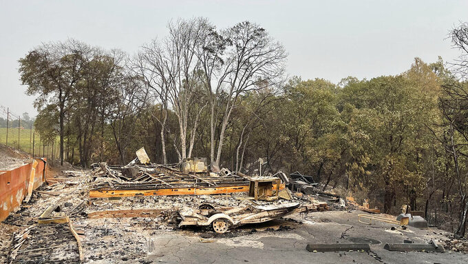 """Charred metal and ash are all that remain of """"Pete"""" Reyna's Chicago Park home which burned Wednesday night due to the River Fire, Aug. 7, 2021. (Elias Funez/The Union via AP)"""