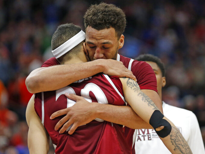 New Mexico State's Trevelin Queen (20) receives a hug from teammate Johnny McCants, rear, at the end of their first round men's college basketball game against Auburn in the NCAA Tournament, Thursday, March 21, 2019, in Salt Lake City. (AP Photo/Rick Bowmer)