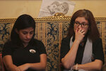 """In this Nov. 17, 2019 photo, Mona, left, and Nada, sisters of Nadyn Jouny, attend a 40 day mourning ceremony of her death in a car accident, at their family house in southern Beirut, Lebanon. In death as in life, Jouny -- affectionately called Om Karam, Arabic for """"mother of Karam"""" -- has showcased the struggles of Lebanese women who are battling laws that give religious courts say over many aspects of their lives. Drawing depicts Jouny with her son Karam. (AP Photo/Hassan Ammar)"""