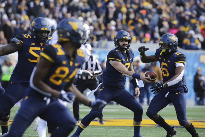 West Virginia quarterback Will Grier (7) hands the ball off to running back Kennedy McKoy (6) during the first half of an NCAA college football game against TCU, Saturday, Nov. 10, 2018, in Morgantown, W.Va. (AP Photo/Raymond Thompson)
