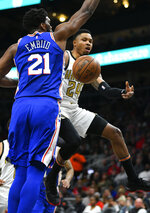 Atlanta Hawks guard Kent Bazemore, right, passes as Philadelphia 76ers center Joel Embiid (21) defends during the first half of an NBA basketball game Saturday, March 23, 2019, in Atlanta. (AP Photo/John Amis)