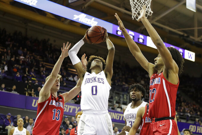 Washington forward Jaden McDaniels (0) shoots between Arizona forwards Stone Gettings, left, and Zeke Nnaji during the first half of an NCAA college basketball game Thursday, Jan. 30, 2020, in Seattle. (AP Photo/Ted S. Warren)