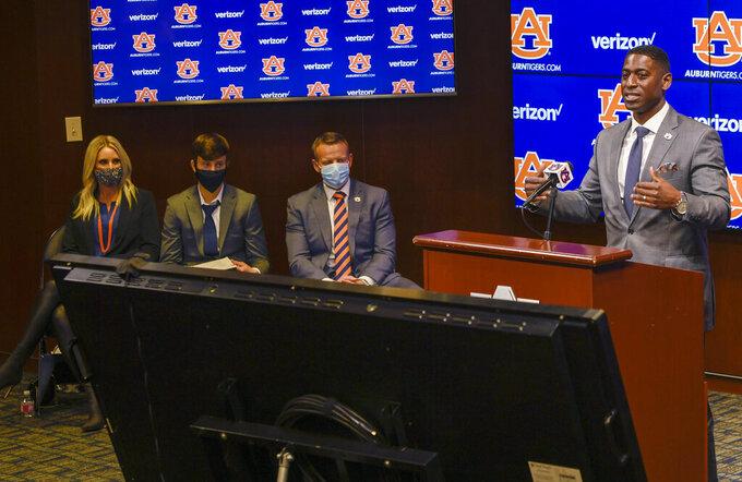 In this photo provided by Auburn Athletics, Auburn athletic director Allen Greene, right, introduces Bryan Harsin, third from left, Auburn's new football coach, Thursday, Dec. 24, 2020, in Auburn, Ala. (Todd Van Emst via AP)
