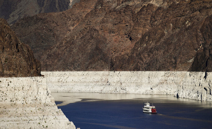 FILE - In this Oct. 14, 2015, file photo, a riverboat glides through Lake Mead on the Colorado River at Hoover Dam near Boulder City, Nev.  The Bureau of Reclamation is forecasting first-ever water shortages because of falling levels at Lake Mead and says the reservoir could drop so low that it might not be able to generate electricity at Hoover Dam.(AP Photo/Jae C. Hong, File)