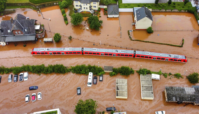 FILE - In this Thursday, July 15, 2021, 2021 file photo, a regional train in the flood waters at the local station in Kordel, Germany, after it was flooded by the high waters of the Kyll river. This summer a lot of the places hit by weather disasters are not used to getting extremes and many of them are wealthier, which is different from the normal climate change victims. That includes unprecedented deadly flooding in Germany and Belgium, 116-degree heat records in Portland, Oregon and similar blistering temperatures in Canada, along with wildfires. Now Southern Europe is seeing scorching temperatures and out-of-control blazes too. And the summer of extremes is only getting started. Peak Atlantic hurricane and wildfire seasons in the United States are knocking at the door. (Sebastian Schmitt/dpa via AP, File)
