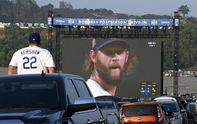 FILE - A fan watches the World Series Game 1 between the Tampa Bay Rays and the Los Angeles Dodgers in the parking lot of Dodger Stadium in Los Angeles in this Tuesday, October 20, 2020, file photo. Sports events held amid the coronavirus pandemic have become a whole different sort of spectacle when it comes to spectators.(Keith Birmingham/The Orange County Register via AP, File)