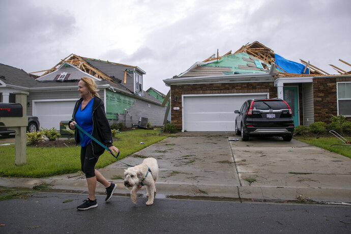 Kathy Desiderio took advantage of a calm between burst of rain to walk her dog Lily and survey the tornado damage at her neighbor's homes. A tornado touched down in the The Farm at Brunswick County in Carolina Shores, N.C. on Thursday, Sept. 5, 2019, damaging homes ahead of Hurricane Dorian's arrival. (Jason Lee/The Sun News via AP)