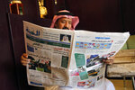 A man reads the daily Al-Madina newspaper fronted by a picture of Saudi King Salman at a coffee shop in Jiddah, Saudi Arabia, Saturday, Dec. 7, 2019. U.S. law enforcement officials were digging into the background of the suspected Florida naval station shooter Friday, to determine the Saudi Air Force officer's motive and whether it was connected to terrorism. Arabic at top reads
