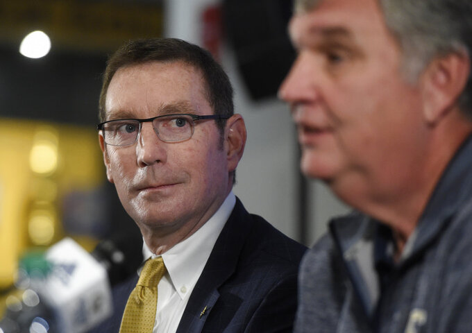 Georgia Tech athletic director Todd Stansbury, left, looks at Paul Johnson during a press conference about Johnson's retirement, Thursday, Nov. 29, 2018, in Atlanta. Johnson, the longest-serving Georgia Tech NCAA college football coach in a half-century, announced his retirement Wednesday after 11 seasons with the team. (AP Photo/Annie Rice)