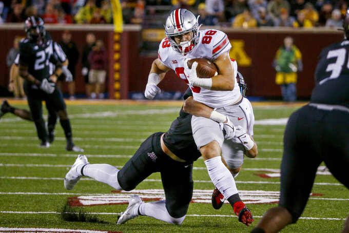 Minnesota linebacker Jack Gibbens tackles Ohio State tight end Jeremy Ruckert (88) during the second quarter of an NCAA college football game Thursday, Sept. 2, 2021, in Minneapolis. Ohio State won 45-31. (AP Photo/Bruce Kluckhohn)
