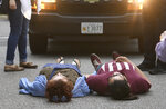 A pair of Hopkins students lay in the road in front of a police van carrying fellow protestors, Wednesday, May 8, 2019. Baltimore police arrested seven people as they ended a monthlong sit-in in the lobby of an administrative building at Johns Hopkins University, where protesters have demonstrated against the creation of a campus police force and the institution's contracts with the U.S. Immigrations and Customs Enforcement agency. (Jerry Jackson/The Baltimore Sun via AP)