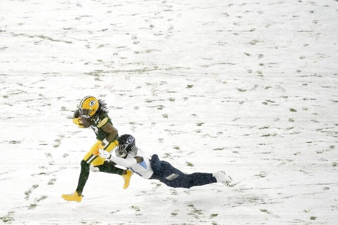 Green Bay Packers' Davante Adams tries to get past Tennessee Titans' David Long during the first half of an NFL football game Sunday, Dec. 27, 2020, in Green Bay, Wis. (AP Photo/Morry Gash)
