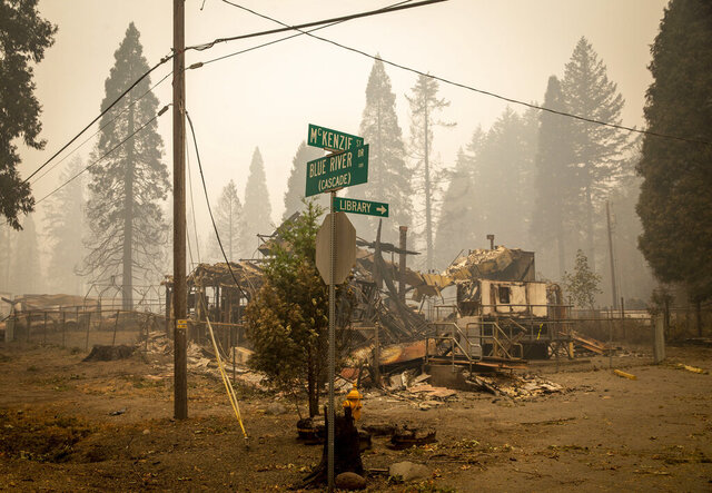 FILE - In this Sept. 15, 2020, file photo, scorched property stands at an intersection in Blue River, Ore., days after a blaze known as the Holiday Farm Fire swept through the area's business district. Oregonians are grieving the loss of some of their most treasured natural places after wildfires wiped out campgrounds, hot springs and wooded retreats that have been a touchstone for generations in a state known for its unspoiled beauty. (Andy Nelson/The Register-Guard via AP, Pool, File)