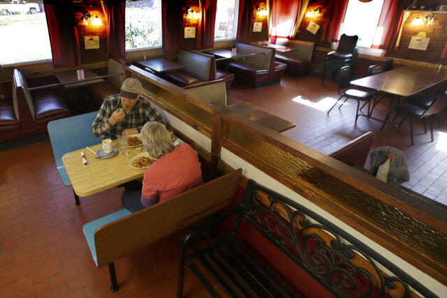 Customers Randy and Nancy Cree eat dinner in the dining room of the Chic-A-Dee Cafe In Topeka, Kan., Tuesday, May 5, 2020. Some booths are closed in order to maintain distance. Restaurant dining rooms, retail stores and some offices began reopening Monday after Kansas lifted a statewide stay-at-home order. (AP Photo/Orlin Wagner)