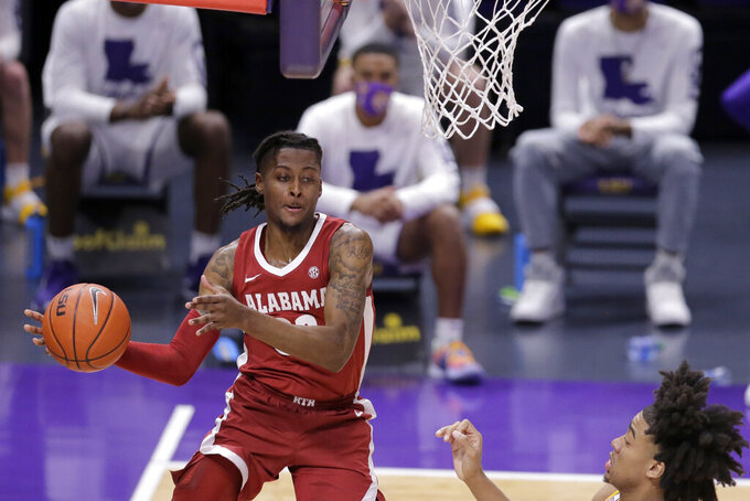 Alabama guard John Petty Jr. passes the ball as LSU forward Trendon Watford defends during the first half of an NCAA college basketball game in Baton Rouge, La., Tuesday, Jan. 19, 2021. (AP Photo/Brett Duke)