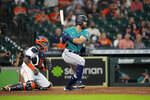 Seattle Mariners' Jose Marmolejos, right, hits a two-run single as Houston Astros catcher Martin Maldonado watches during the ninth inning of a baseball game Wednesday, Sept. 8, 2021, in Houston. (AP Photo/David J. Phillip)