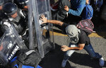 A migrant charges on Mexican National Guardsmen at the border crossing between Guatemala and Mexico in Tecun Uman, Saturday, Jan. 18, 2020. More than a thousand Central American migrants surged onto a bridge spanning the Suchiate River that marks the border between both countries as Mexican security forces attempted to impede their journey north. (AP Photo/Marco Ugarte)