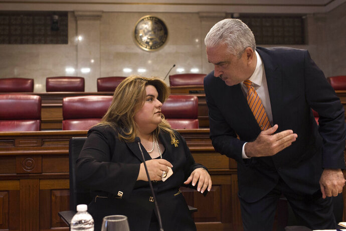 Commissioner Jenniffer Gonzalez listens to Puerto Rico Senate President Thomas Rivera Schatz, before a private meeting with Legislators and Mayors, in San Juan, Puerto Rico, Thursday, Aug. 8, 2019. Rivera Schatz, who played a key role in the successful court challenge to the swearing-in last Friday of Pedro Pierluisi after then-Gov. Ricardo Rossello resigned, publicly backed Gonzalez, Puerto Rico's representative to the U.S. Congress, to become governor. (AP Photo/Dennis M. Rivera Pichardo)
