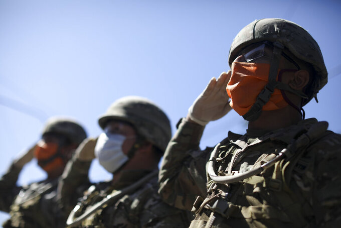 Soldiers sing their national anthem at a soup kitchen where they delivered food on the outskirts of Buenos Aires, Argentina, Thursday, April 2, 2020, during a government-ordered lock down to help contain the spread of the new coronavirus. (AP Photo/Natacha Pisarenko)