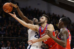 Villanova's Dhamir Cosby-Roundtree, left, blocks a shot by DePaul's Max Strus, center, as Paul Reed looks on during the first half of an NCAA college basketball game, Wednesday, Jan. 2, 2019, in Villanova, Pa. (AP Photo/Matt Slocum)