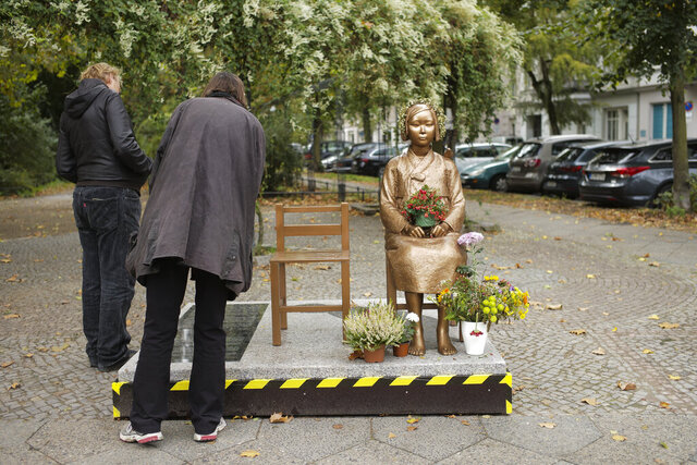 People read the inscription of a statue commemorating so-called 'comfort women', an euphemism given by Japan to the women and girls enslaved for sex by the Japanese army during World War II, displayed at a residential area in central Berlin, Germany, Friday, Oct. 9, 2020. (AP Photo/Markus Schreiber)