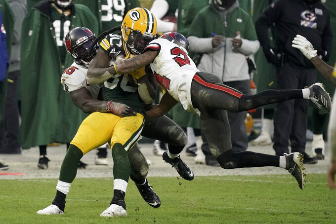 Green Bay Packers' Jamaal Williams is stopped by Tampa Bay Buccaneers' Carlton Davis (24) and Devin White during the second half of the NFC championship NFL football game in Green Bay, Wis., Sunday, Jan. 24, 2021. (AP Photo/Morry Gash)